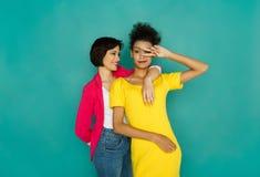 Twee glimlachende meisjes die pret hebben bij de achtergrond van de azurstudio Stock Afbeelding