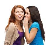 Twee glimlachende meisjes die roddel fluisteren Stock Foto