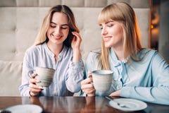 Twee glimlachende meisjes drinkt koffie in koffie Stock Foto