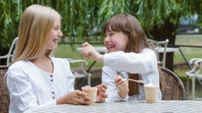 Twee glimlachende meisjes of Gelukkige kinderen met roomijs in openlucht stock video