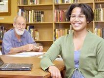Twee glimlachende mensen, Europese oude mens en Afrikaans meisje, in librar Stock Fotografie