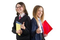 Twee glimlachende middelbare schoolmeisjes in eenvormige dragende glazen met notitieboekjes die duim tonen ondertekenen omhoog o. stock afbeeldingen