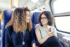 Twee glimlachende mooie meisjes die een smartphone gebruiken Stock Afbeeldingen