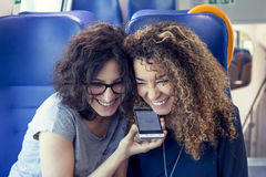Twee glimlachende mooie meisjes die een smartphone gebruiken Royalty-vrije Stock Foto's