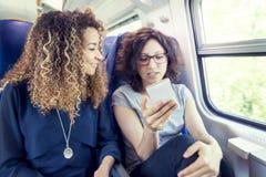 Twee glimlachende mooie meisjes die een smartphone gebruiken Stock Fotografie