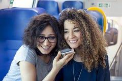 Twee glimlachende mooie meisjes die een smartphone gebruiken Royalty-vrije Stock Foto