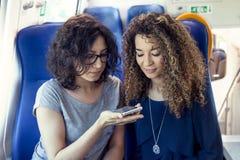 Twee glimlachende mooie meisjes die een smartphone gebruiken Stock Foto's