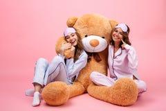 Twee glimlachende mooie meisjes kleedden zich in pyjama's Stock Foto