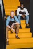 twee glimlachende multi-etnische eigenaars van koffiewinkel in schorten het zitten stock foto's