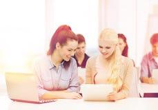 Twee glimlachende studenten met laptop en tabletpc stock foto