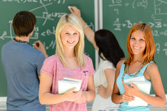 Twee glimlachende studentenmeisjes in wiskundeklasse Stock Afbeeldingen