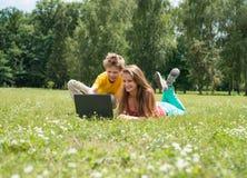 Twee glimlachende tienersstudenten met laptop die op weide rusten Onderwijs technologie royalty-vrije stock fotografie