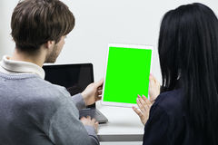 Twee glimlachende toevallige ontwerpers die met laptop en tablet in het bureau werken Het groene scherm Stock Fotografie