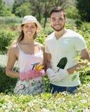 Twee glimlachende volwassenen in bloementuin Stock Foto's