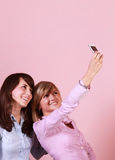 Twee glimlachende vrienden die celtelefoon voor een foto met behulp van Royalty-vrije Stock Afbeeldingen
