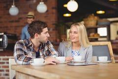 Twee glimlachende vrienden die en koffie spreken drinken royalty-vrije stock foto
