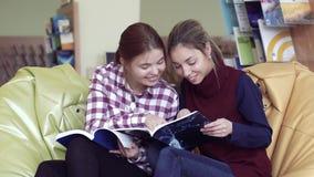 Twee glimlachende vrouwelijke studenten die door grappige tijdschriften beduimelen stock footage