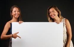 Twee glimlachende vrouwen die een lege banner houden stock afbeeldingen