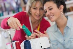 Twee glimlachende vrouwen die naaimachine met behulp van terwijl het houden van heldere stof stock foto's