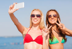 Twee glimlachende vrouwen die selfie op strand maken Royalty-vrije Stock Fotografie