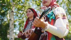 Twee glimlachende vrouwen in Russische kleding bevinden zich onder een berk boom en het zingen samen met een balalaika stock footage