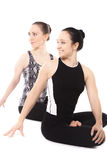 Twee glimlachende Yogimeisjes die in yoga Lotus Pose ontspannen Stock Afbeeldingen