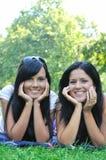 Twee glimlachende zusters die in openlucht liggen royalty-vrije stock foto's