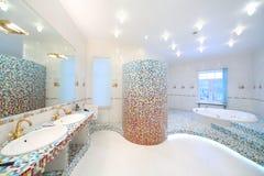 Twee gootstenen en grote spiegel in ruime badkamers met Jacuzzi stock fotografie