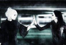 Twee gothvrouwen wat betreft handen stock afbeeldingen
