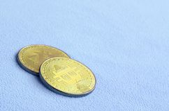 Twee gouden die bitcoins ligt op een deken van zachte en pluizige lichtblauwe vachtstof wordt gemaakt Fysieke visualisatie van vi stock afbeelding