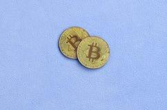 Twee gouden die bitcoins ligt op een deken van zachte en pluizige lichtblauwe vachtstof wordt gemaakt Fysieke visualisatie van vi royalty-vrije stock afbeeldingen
