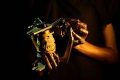 Twee gouden handen met een tandinstrument op een zwarte achtergrond stock afbeeldingen