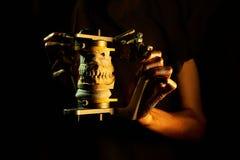 Twee gouden handen met een tandinstrument op een zwarte achtergrond stock afbeelding
