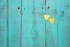 Twee gouden harten die op antieke wintertalings blauwe houten omheining hangen Stock Afbeelding