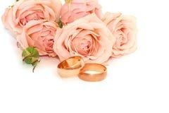 Twee gouden ringen en rozen op witte achtergrond Royalty-vrije Stock Foto