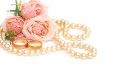 Twee gouden ringen, parels en bloemen Stock Afbeelding
