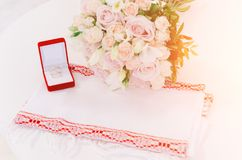 Twee gouden ringen in rode doos dichtbij mooie creamerozen op witte achtergrond Stock Afbeeldingen