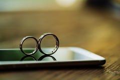 Twee gouden ringen zijn op de telefoon in de ruimte De ringen in de vorm van acht worden getoond op de achtergrond van het scherm royalty-vrije stock fotografie