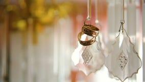 Twee gouden trouwringen die met licht glanzen Macrotransfusie van licht op ringen stock video