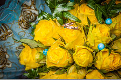 Twee gouden trouwringen en gele rozen Stock Foto