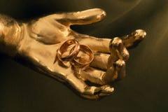 Twee gouden trouwringen in gouden hand Stock Afbeelding