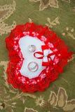 Twee gouden trouwringen liggen op een kussen in de vorm van een hart met een rood kant Stock Afbeeldingen