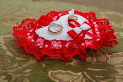Twee gouden trouwringen liggen op een kussen in de vorm van een hart met een rood kant Royalty-vrije Stock Foto