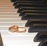 Twee gouden trouwringen op piano royalty-vrije stock afbeelding