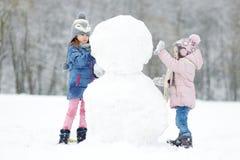 Twee grappige aanbiddelijke kleine zusters in de winterpark stock afbeeldingen
