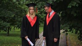 Twee grappige gediplomeerden die en rond in park na graduatie dansen voor de gek houden stock videobeelden