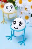Twee grappige het glimlachen eieren op tribunes en bloemen Royalty-vrije Stock Afbeelding