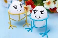 Twee grappige het glimlachen eieren op tribunes en bloemen, selectieve nadruk Stock Foto