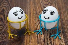Twee grappige het glimlachen eieren op tribunes, op een houten lijst Stock Fotografie