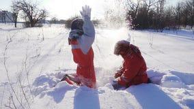Twee grappige jonge geitjes die sneeuw samen werpen stock video